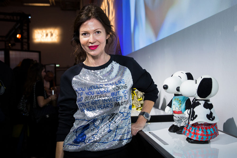 A brunette woman, wearing a sparkly, silver shirt, is standing beside two, small black and white dog statues at an indoor event.