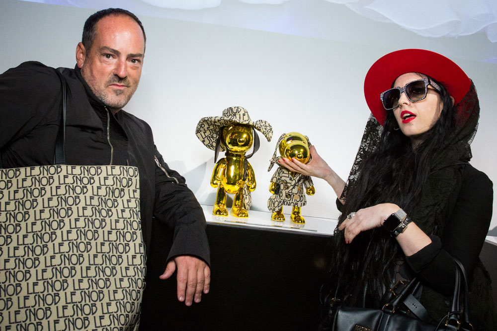 A man and woman posing for a photo at an event. The man on the left is wearing a black jacket and a big purse. The girl on the left is wearing a red hat, black clothes and touching a gold statues beside her.