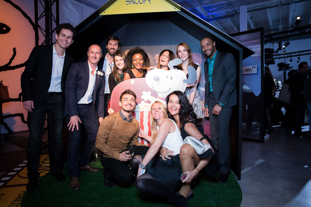 A large group of people dressed in semi formal attire posing for a photo at an indoor event, in front of a large playhouse.