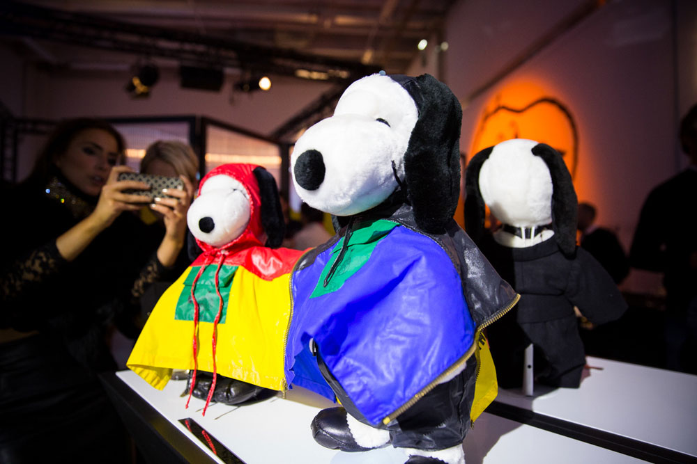 A close-up of black and white dog statues on display, wearing colourful raincoats.