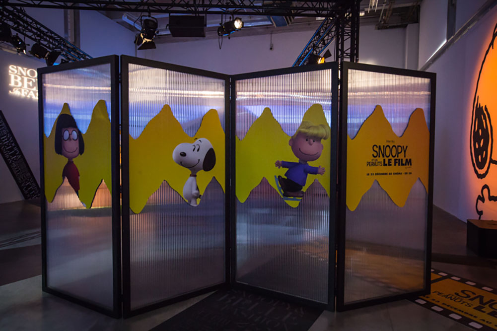 An indoor space with a large glass divider in the middle of it. The divider has cartoon character illustrations on it.
