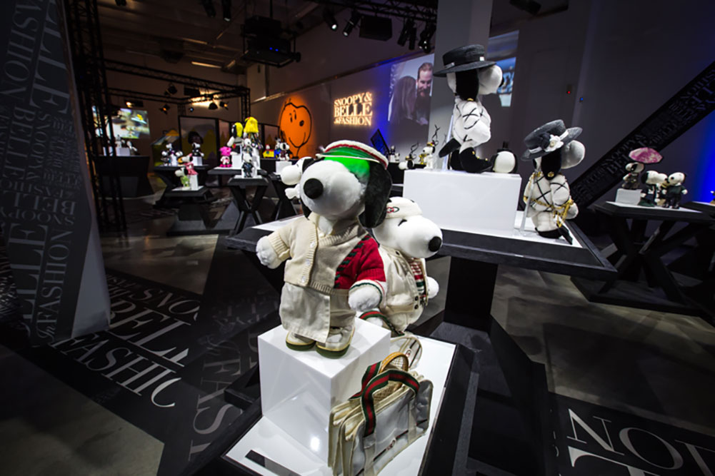 An indoor space displaying black and white dog statues wearing various costumes.