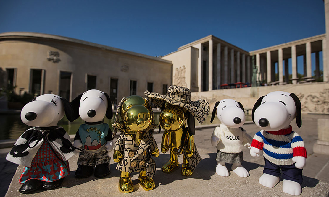 Four black and white dog statues and 2 gold dog statues on a concrete wall with a building in the background.
