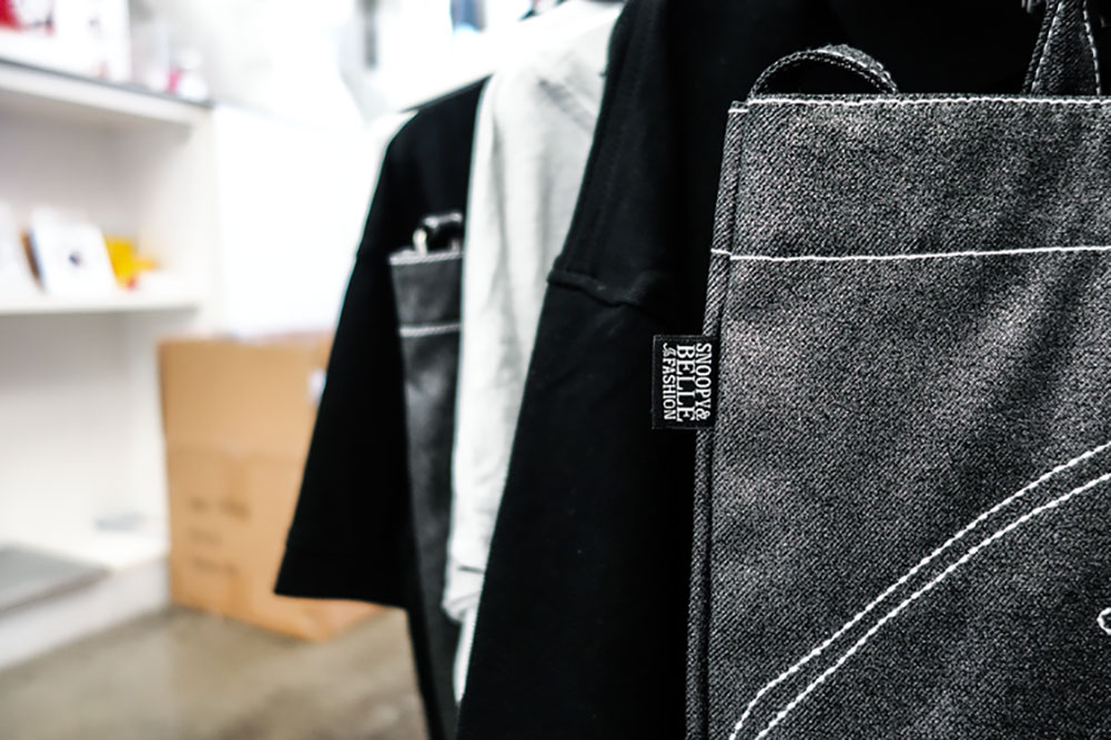 A close up of a label on a grey bag and other merchandise hanging in the background.