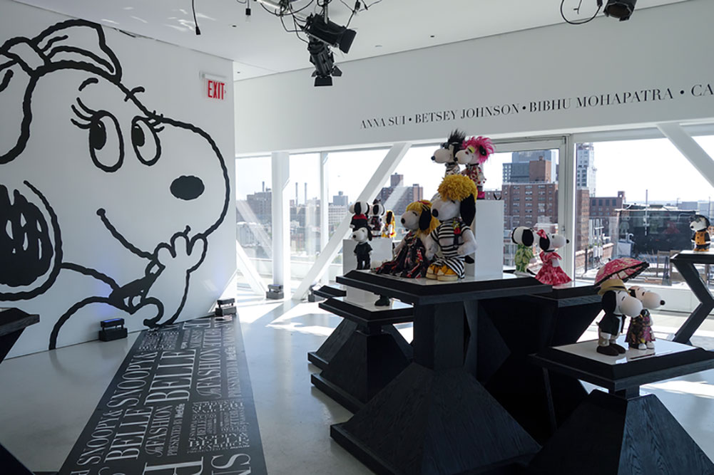 A bright, indoor space with large windows, several tables displaying small black and white dog statues and a large illustration of a dog on the wall.