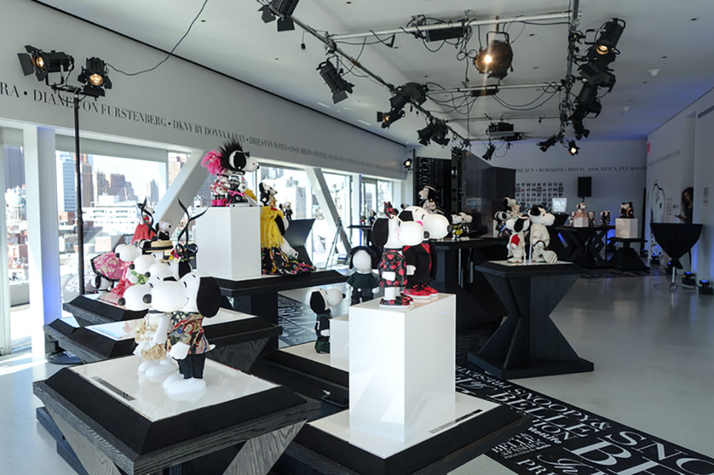 An indoor space with black and white decor and several tables displaying statues of black and white dogs wearing designer costumes.