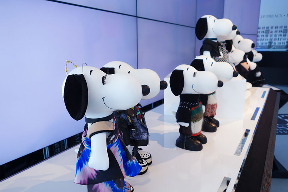 A close-up of small black and white dog statues on display, wearing designer costumes.