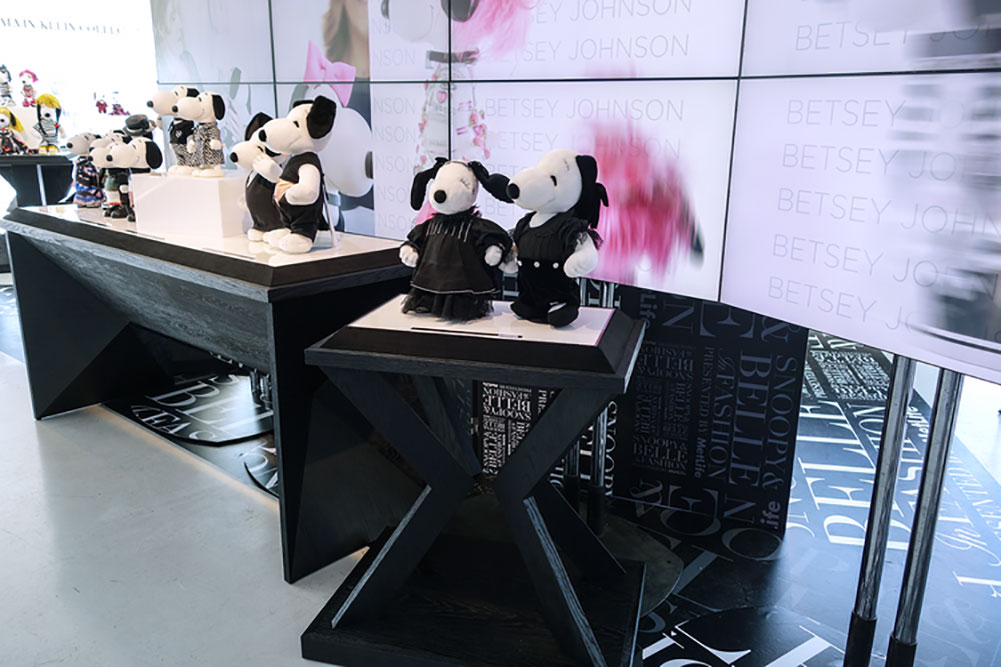 An indoor space with a couple of stands displaying small black and white dog statues wearing designer costumes.