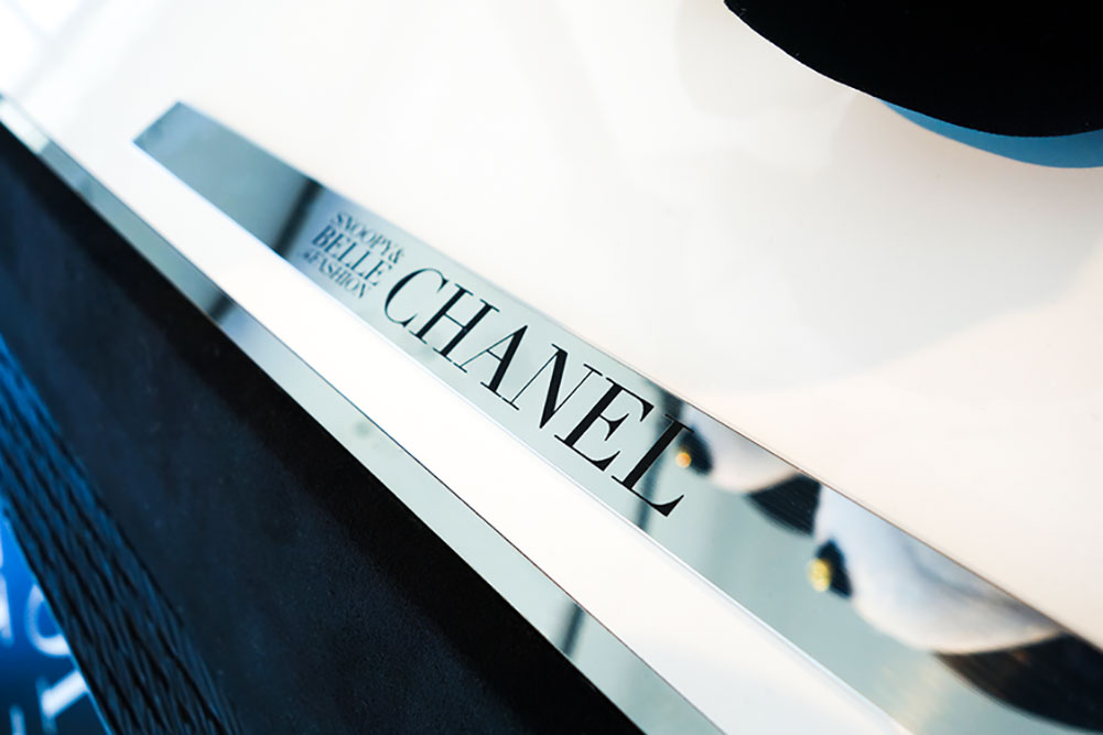 A white surface with a silver label that says: Chanel.