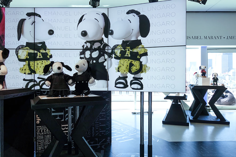 An indoor space with several tables displaying black and white dog statues and a large poster with black and white dogs wearing designer costumes.