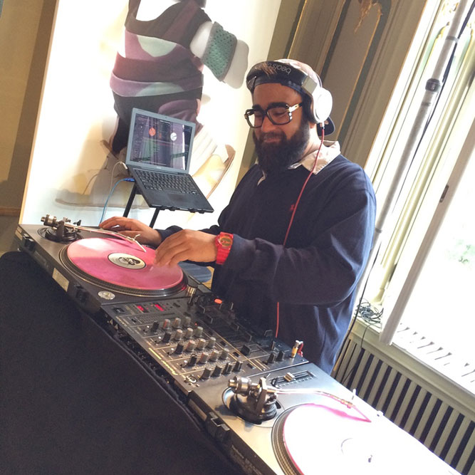 A bearded man with glasses DJing at an indoor event.
