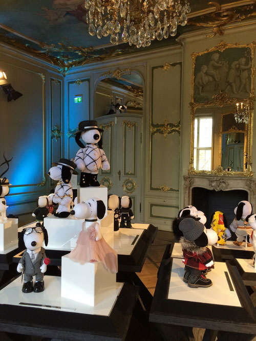 Small black and white dog statues displayed on white tables inside a room with antique furniture and a crystal chandelier.