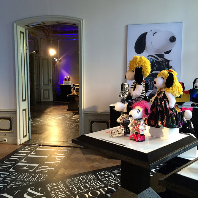 Small black and white dog statues, in various costumes, displayed in a large room. There is a photo on the wall of a black and white dog.