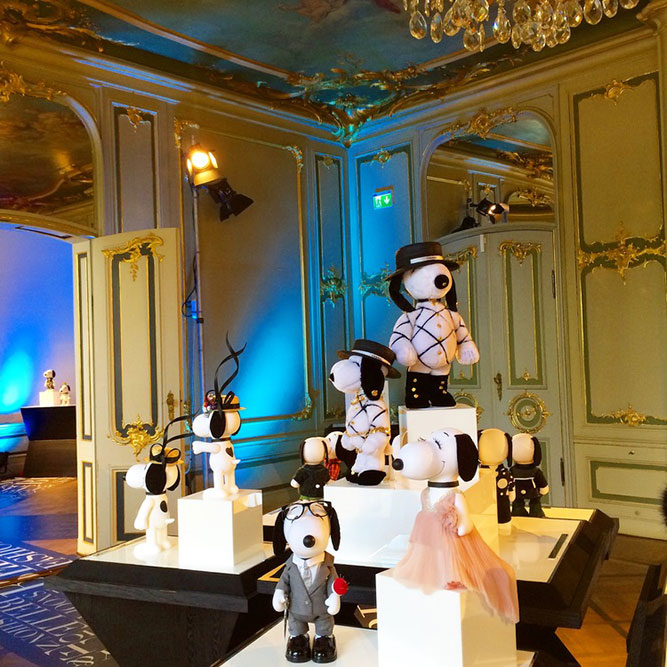 A room with high ceilings and antique decor and small black and white dog statues on display.
