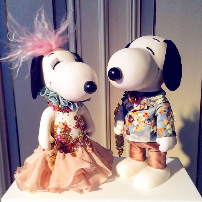 A close-up of two black and white dog statues wearing colourful costumes.