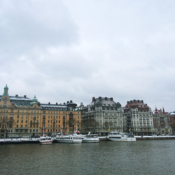 A waterfront, European city on a cloudy day with several boats docked at the pier.