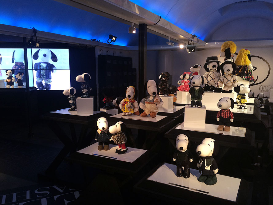 A dark, indoor space displaying small black and white dog statues wearing designer costumes.