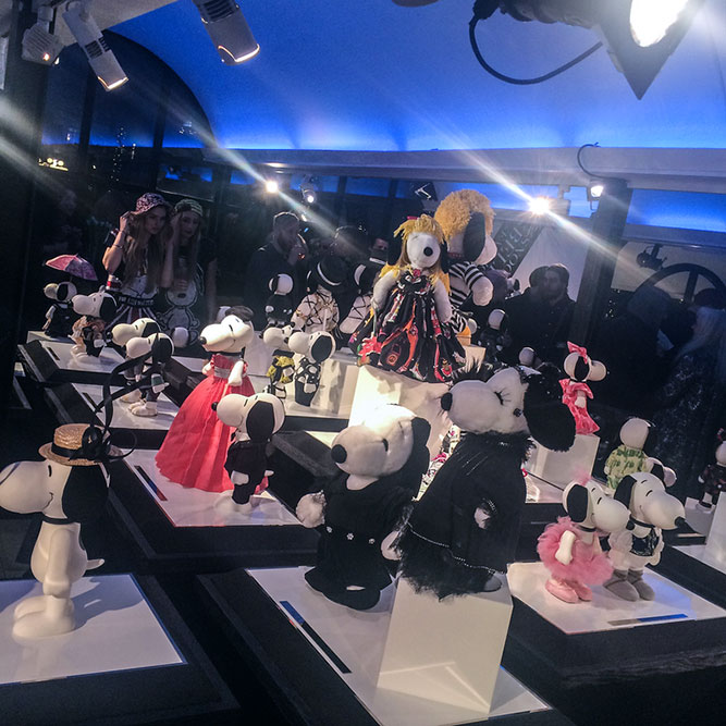 An indoor space displaying small black and white dog statues wearing designer costumes.