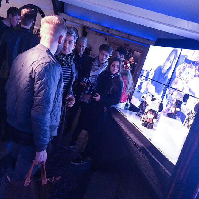 People mingling at an indoor event in front of a large TV screen.