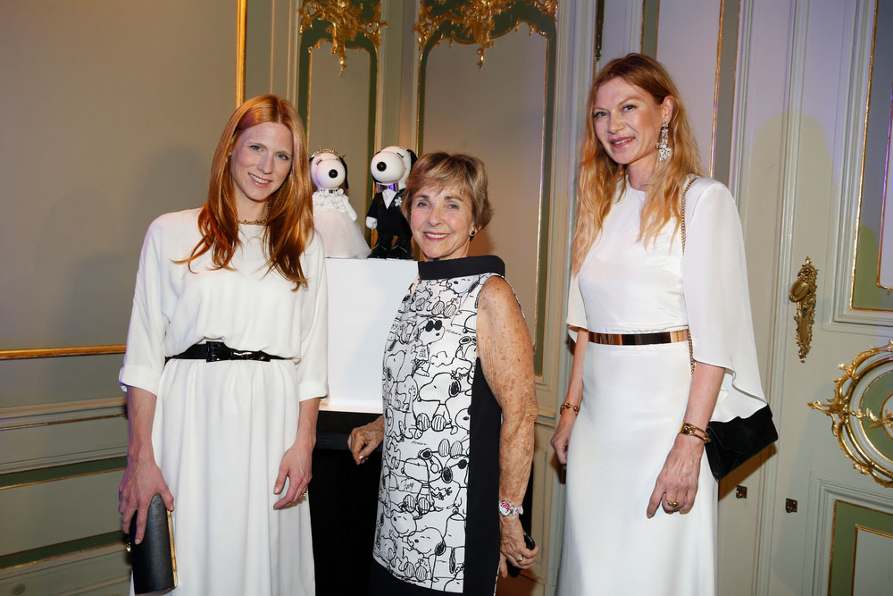 Three women, wearing white and black dresses, posing for a phot at an event.