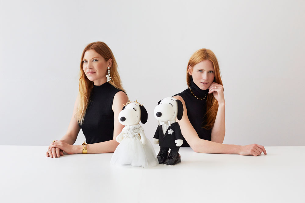 Two women with long red hair, wearing black dresses sitting in behind two black and white dog statues.