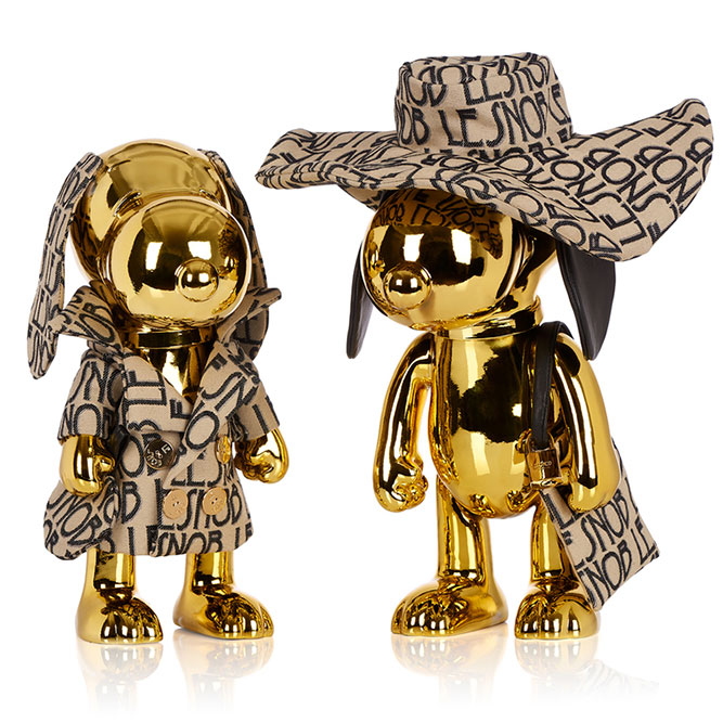 Two gold dog statues in front of a white background wearing matching beige and black outfits.