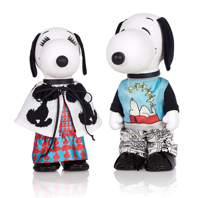Two black and white dog statues in front of a white background. The dog on the left is wearing a red and blue dress with a black and white jacket. The dog on the right is wearing black and white pants with a blue shirt.