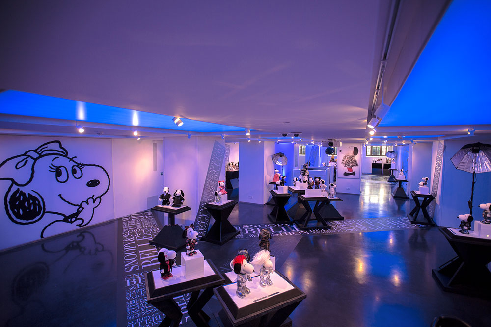 An indoor space with blue lights and several displays of black and white dog statues wearing various outfits.