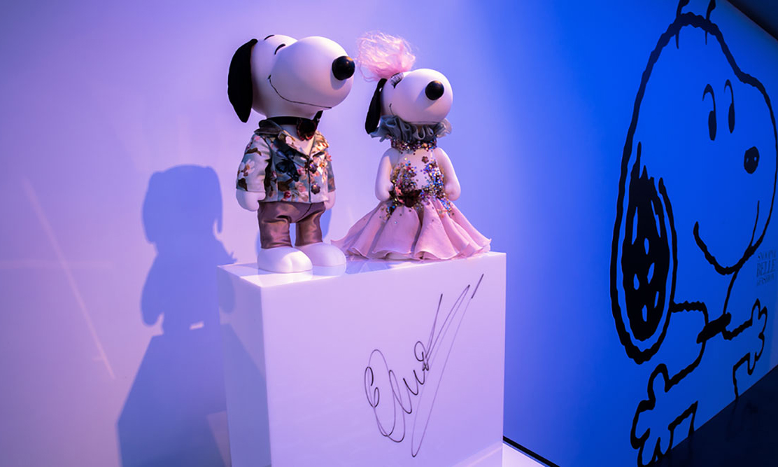 Two black and white dog statues wearing designer outfits on display in a room with blue lights.