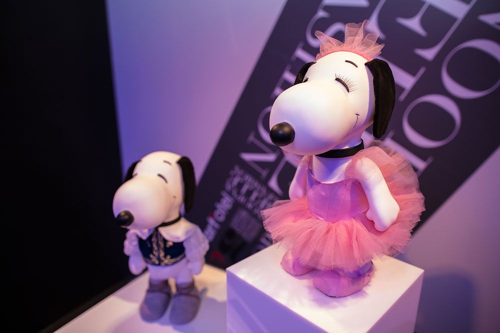 A close-up of two black and white dog statues on display in a room with blue lights. One statue is wearing a pink tulle dress and the other one a white blouse and a vest.