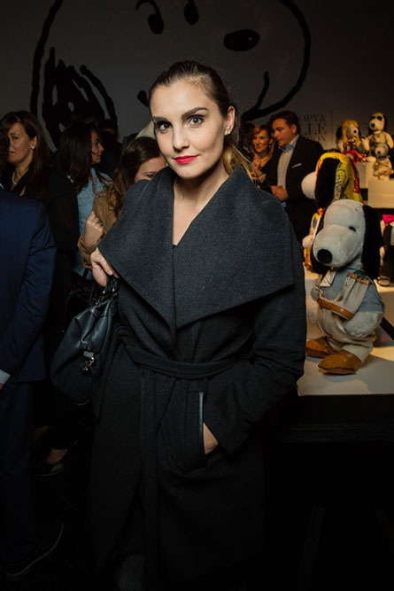 A woman wearing a grey jacket posing for a picture at an event.