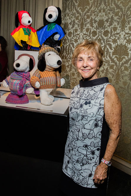 A senior woman, wearing a black and white dress, standing beside a display of black and white dog statues wearing various outfits.