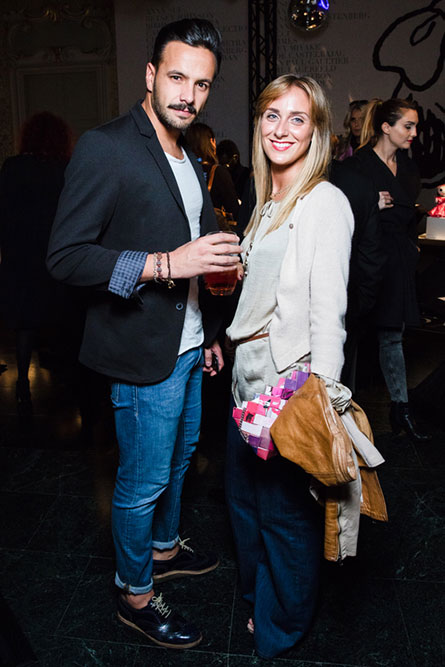 A man wearing jeans and a black suit jacket is standing next to a blonde woman wearing a beige shirt. They are posing for a picture at an event.