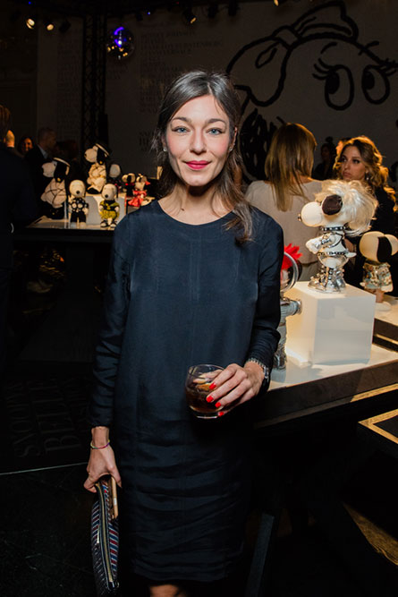 A woman posing for a picture at an event. She is wearing a dark blue dress and holding a drink in her hand. There is an art display behind her.