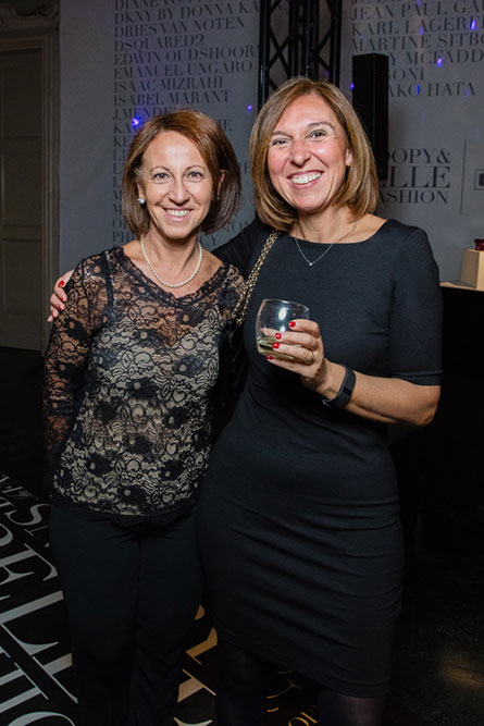 Two middle aged woman, dressed in formal attire, smiling and posing for a picture at an event.