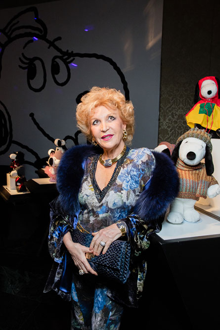 A senior woman, wearing a blue dress is posing for a picture in front of an art display of black and white dog statues.