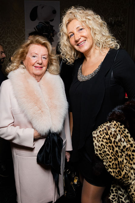 Two blonde, older woman posing for a picture at an event. The women on the left is wearing a light pink coat and the woman on the right is wearing a black dress.