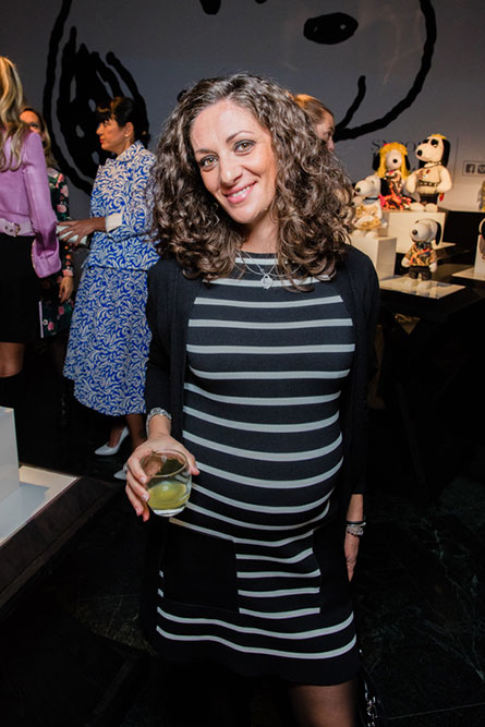 A woman wearing a black and white striped dress, with curly brown hair, is holding a drink in her hand and posing for a photo.