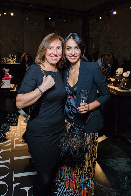 Two women, wearing black cocktail semi-formal attire, posing for a photo at an event.