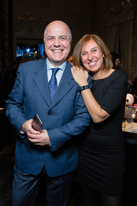 A woman in a black dress leaning against a man wearing a blue suit and smiling for the camera.