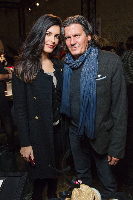 A brunette women in a black coat standing beside a man with long hair and a blue scarf and posing for a photo.