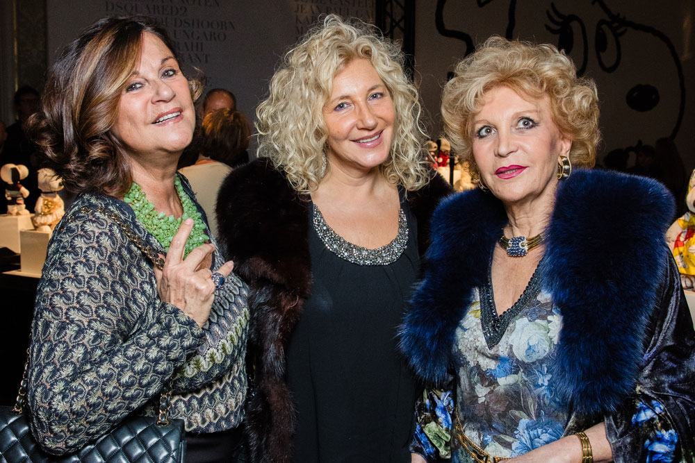 Three middle-aged women, dressed in semi-formal attired, posing for a photo at an event.