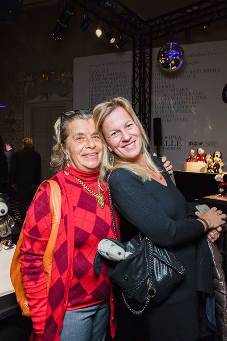 Two blonde women posing for a photo at an event. The women on the left is wearing a red, checkered shirt and the woman on the right is wearing a black dress.