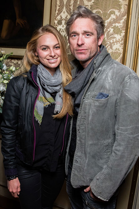 A blonde woman and a grey haired man posing for a photo at an event.