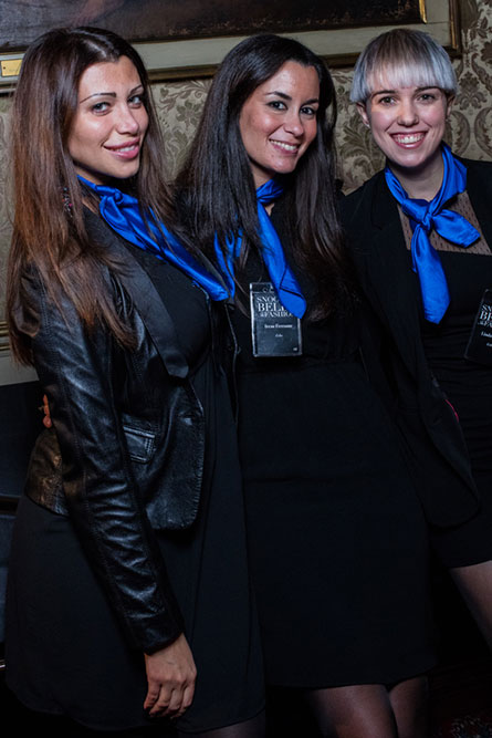 Three women wearing black outfits and blue scarves around their neck posing for a picture.