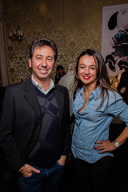 A brunetter woman wearing a denim shirt is standing beside a man wearing a black jacket. They are posing for a photo at an event.