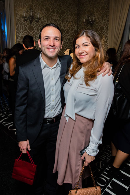 A man and woman, wearing semi-formal attire, posing for a photo at an event.