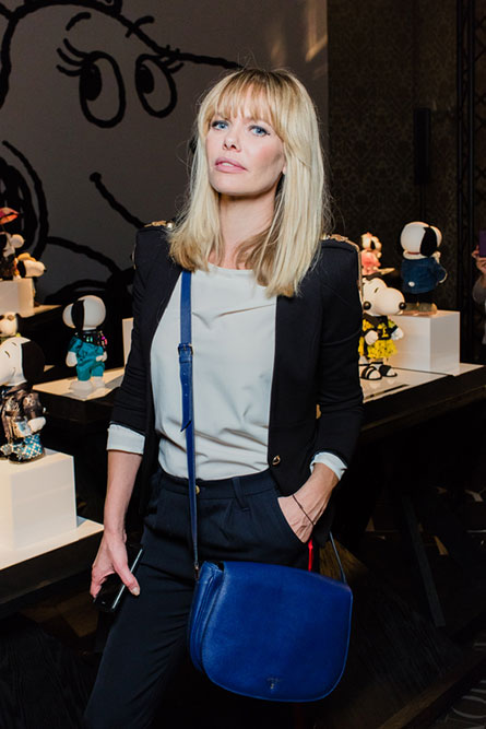 A blonde woman posing for a photo an an event. She is wearing a blue purse, plant pants a black blazer.