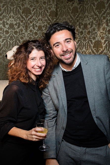 A man and a woman smiling for a photo at an event. The man on the right is wearing a grey suit and the woman is wearing a black dress.