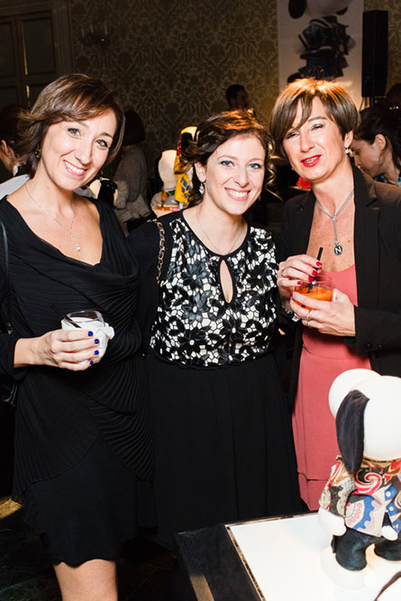 Three women, wearing cocktail dresses, posing for a photo at an event.